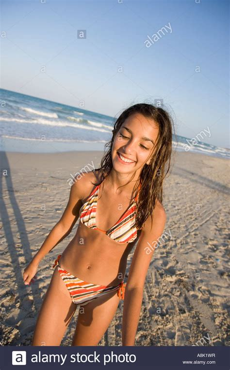 teenage girl wearing bikini walking  beach stock photo
