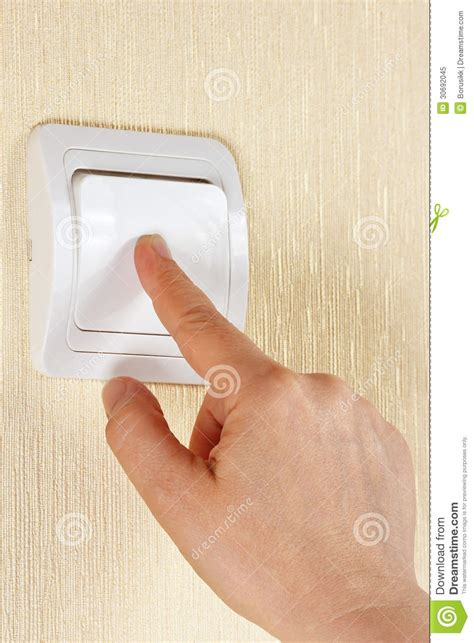 hand turn off the light switch on the wall stock image