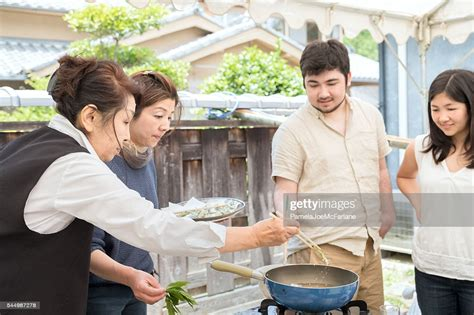 Senior And Mature Japanese Women Teaching Cooking To Young