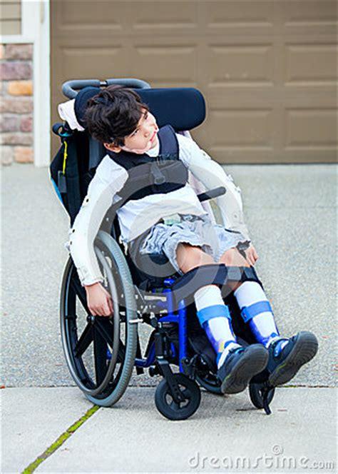 seven year biracial disabled boy in wheelchair stock