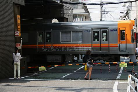 People Wait As Commuter Train Passes Through Street Level