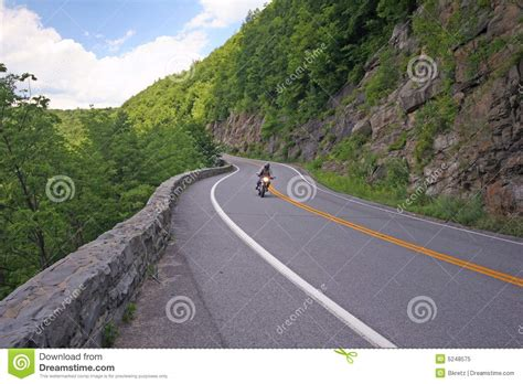 Motorcycle Riding Down Curvy Road. Royalty Free Stock