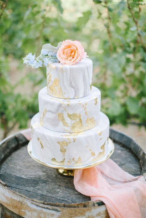 A Beautiful Gray And Gold Marbled Wedding Cake With Peach