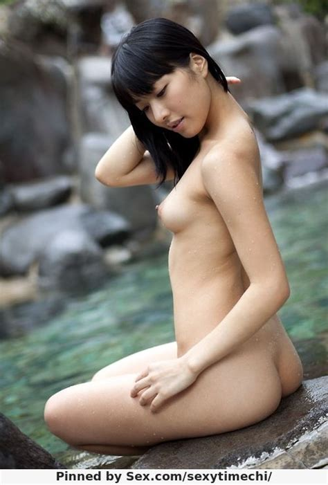 nude japanese woman sitting on side of onsen pool