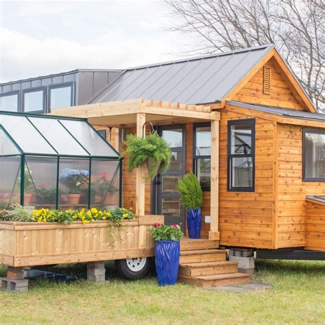 the elsa tiny house has greenhouse and porch swing